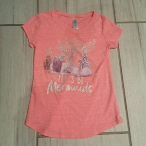 A pink shirt with mermaids on it
